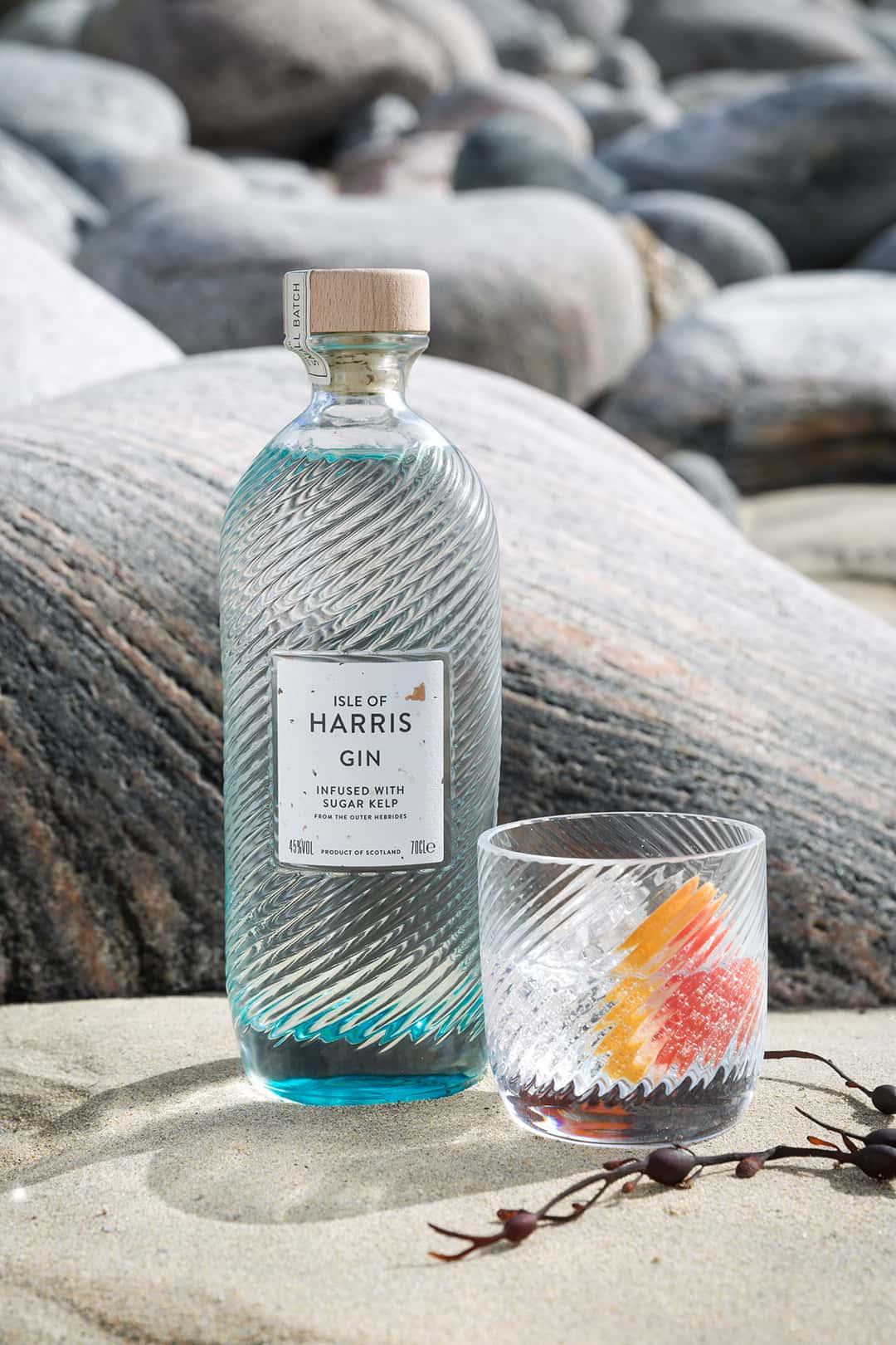 Isle of Harris Gin bottle sitting on sea rocks with a G&T