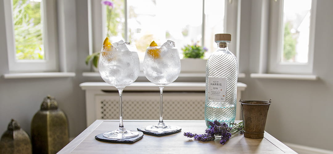2 Isle of Harris G&Ts on a table, along with the Harris Gin bottle