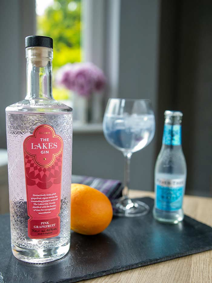 The Lakes Pink Grapefruit Gin bottle, gin and tonic, and a bottle of Fever-Tree Mediterranean Tonic