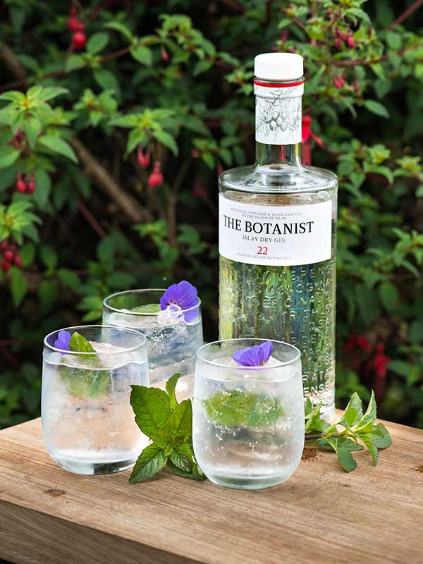 The Botanist Gin bottle and three gin and tonics sitting on an outdoor table.