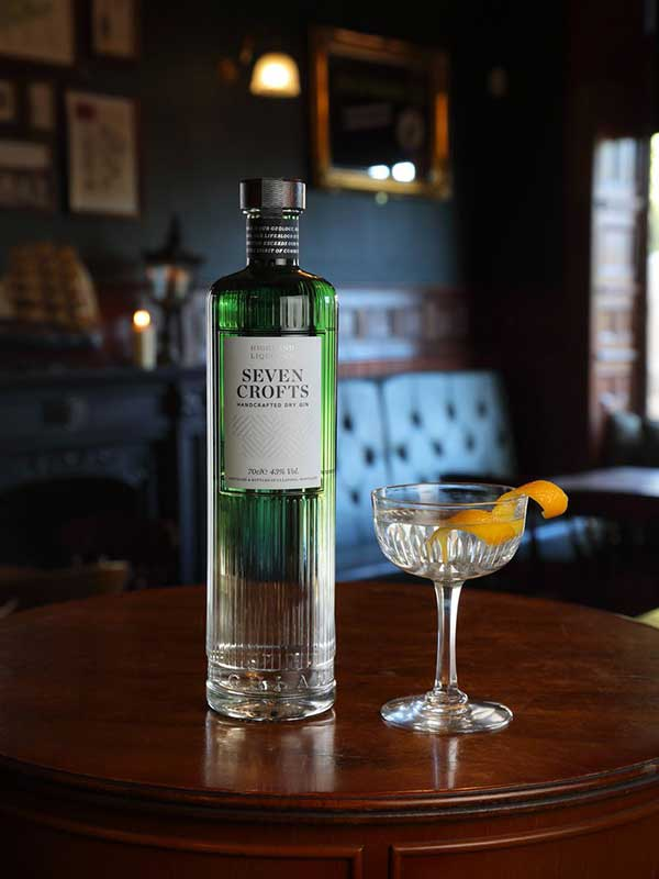Seven Crofts Gin bottle sitting on a table with a gin and tonic, garnished with orange peel.