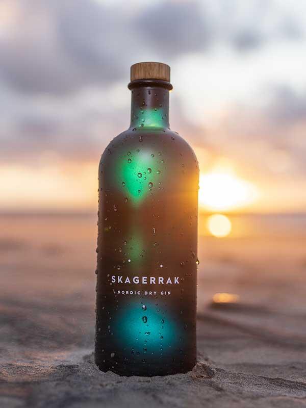 Skagerrak Gin bottle sitting on a beach at sunset.