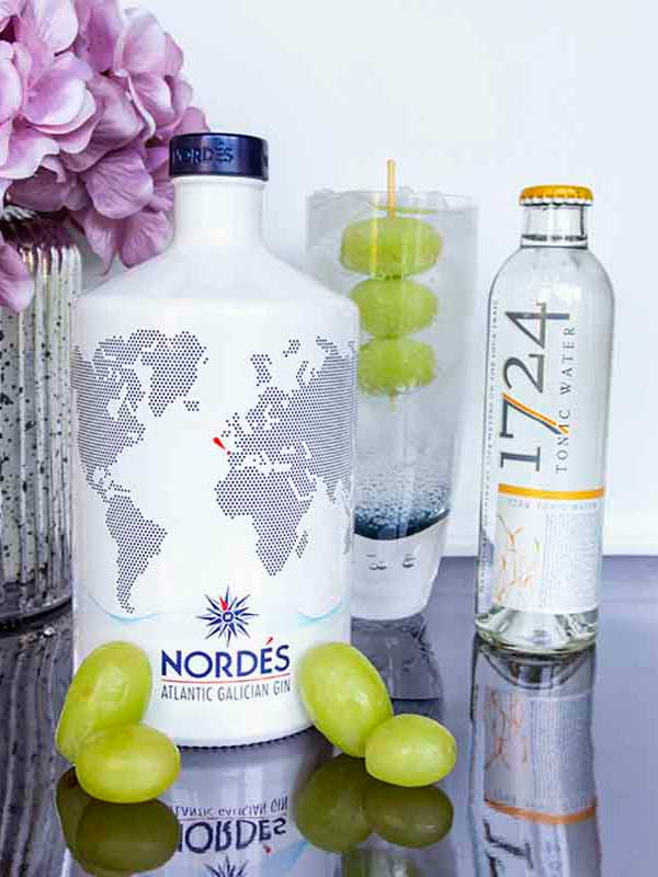 Nordés Gin bottle, with a gin and tonic, garnished with grapes.