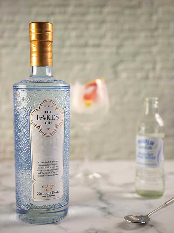 The Lakes Gin bottle. A gin and tonic and tonic water blurred in the background.